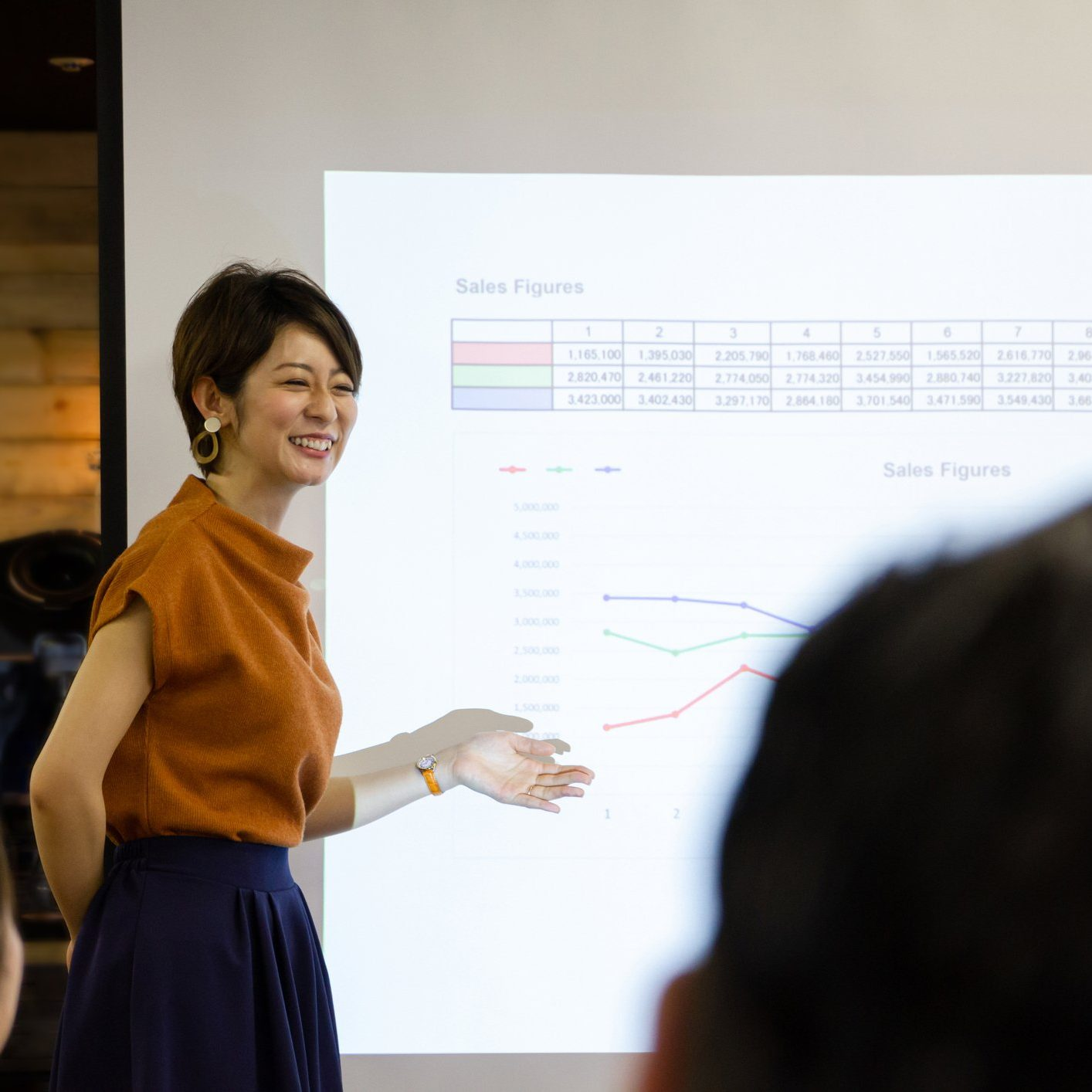 Japanese businesswoman standing by projection screen, giving presentation